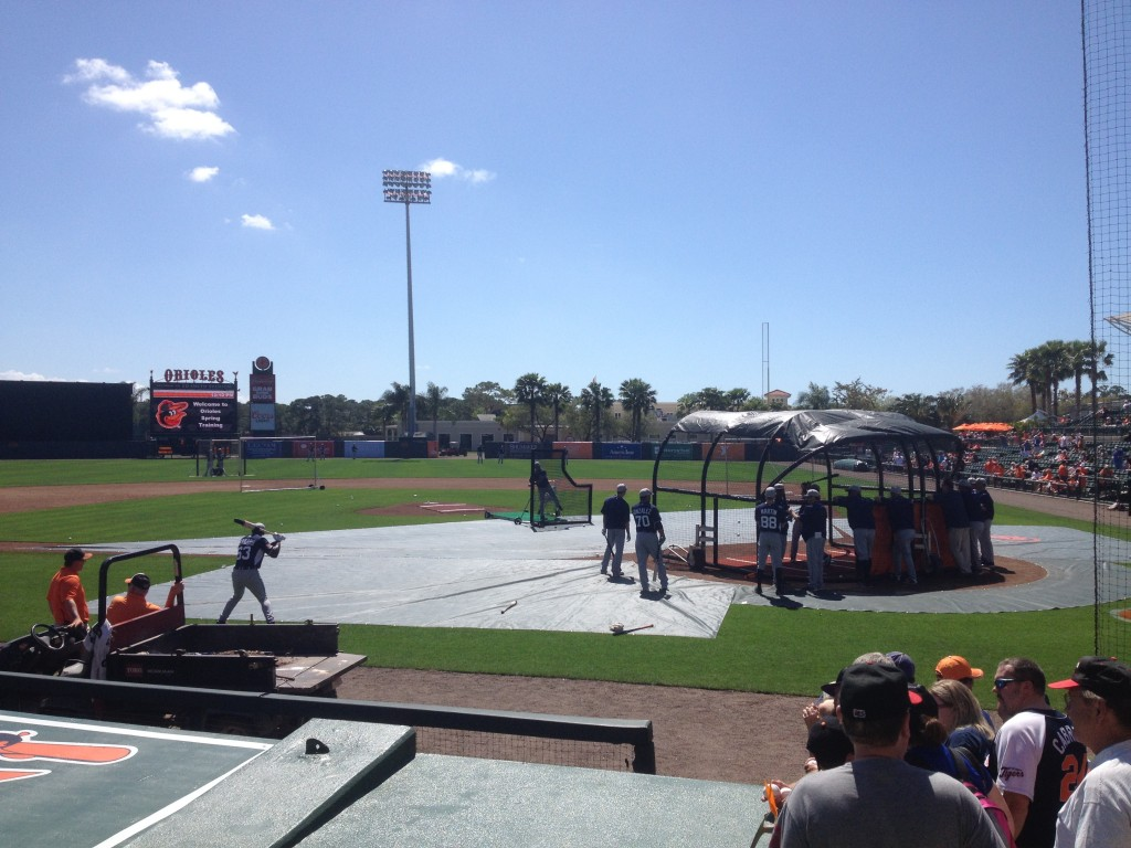 The Jays take BP in the sun while snow falls in Baltimore.